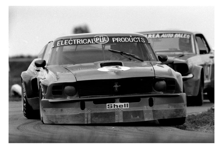 Timaru Motor Raceway 1977. Dave Baker giving the Electric Blue PDL1 Mustang and airing. Here leading Rod McElreas Mustang. The car previously raced by Paul Fahey. IMAGE/terry marshall
