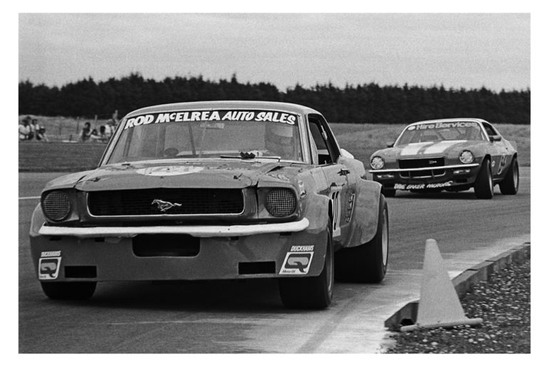 Wigram 1975. The legendary Rod McElrea hustles his OSCA Ford Mustang thru Bomb Bay corner.  Following is Dave Bakers   Z28 Camaro. IMAGE/terry marsha