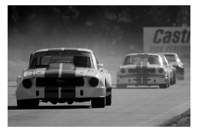 Ruapuna, mid 70's. Bob Slade leads Rod McElrea in matching white and blue Mustangs during one of their many OSCA battles. IMAGE/terry marshall